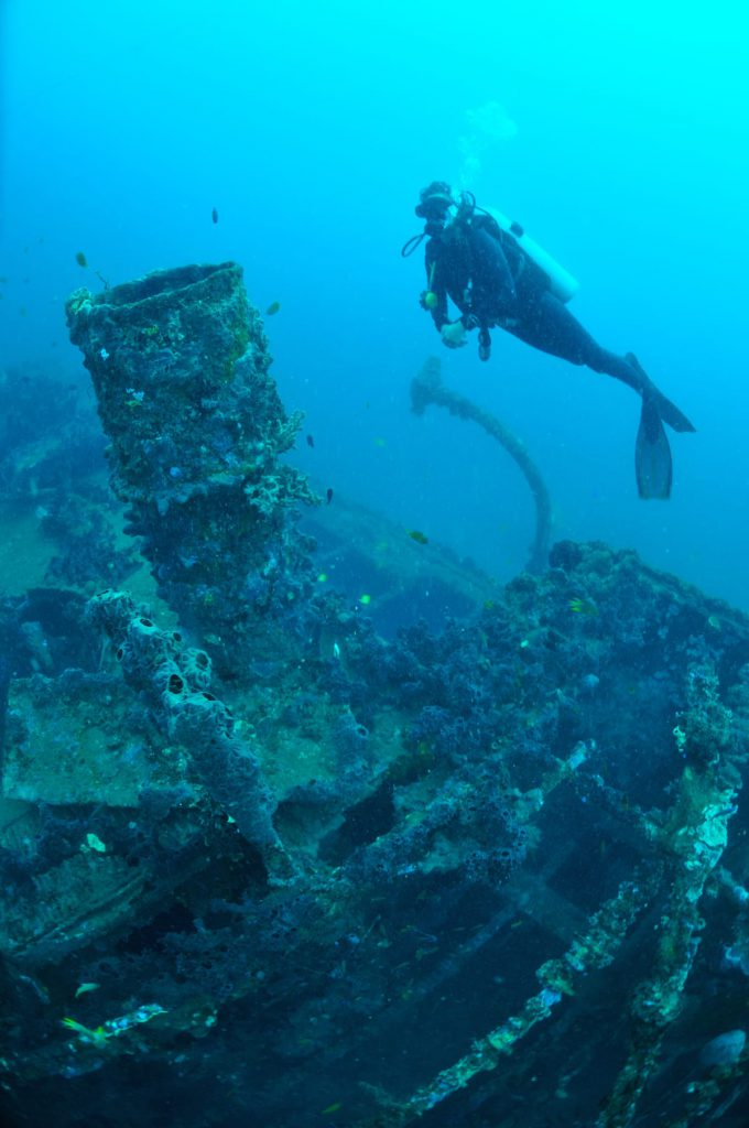 Diver hanging above the wreck — wreck diving North Sulawesi
