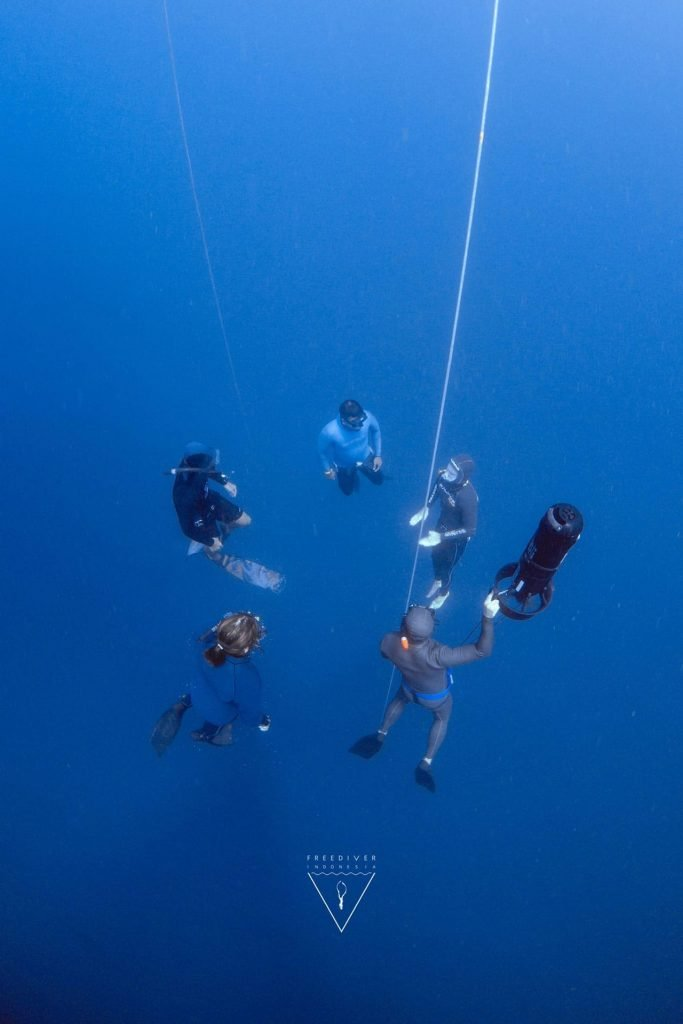 Freediver safety hanging next to the line with waterscooter