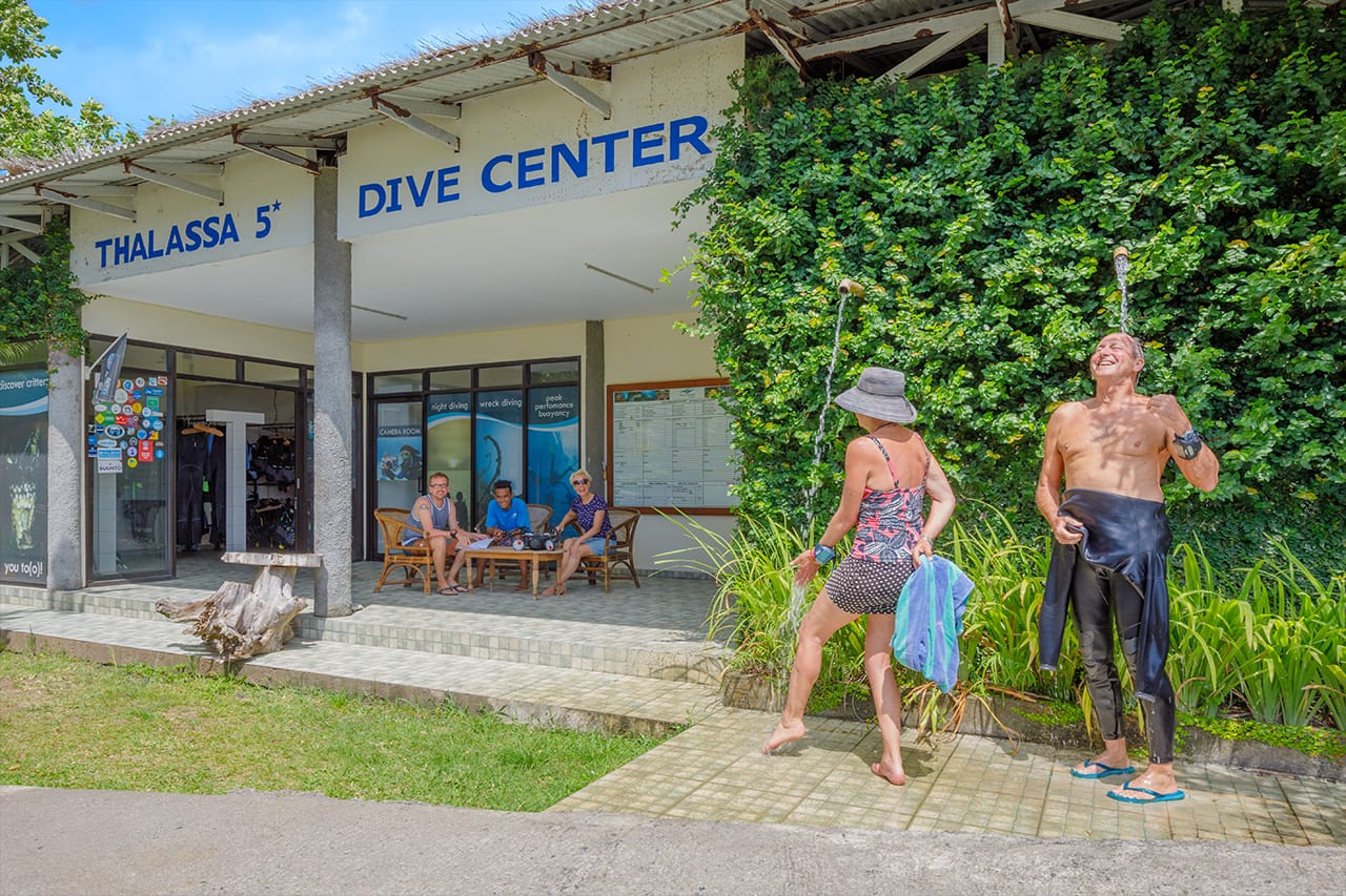 Diving in North Sulawesi — Dive center with divers rinsing off under fresh water showers and people smiling in the background